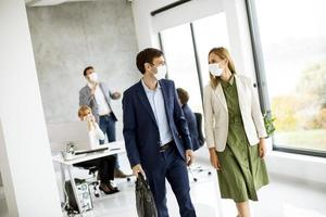 Two masked business professionals walking photo