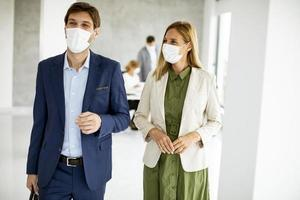 Two masked professionals walking in an office photo