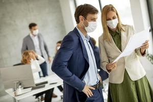 profesionales enmascarados mirando documentos foto
