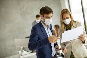Primer plano de profesionales enmascarados mirando un documento foto