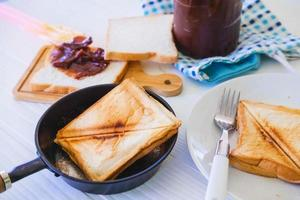 Roasted toast bread popping up of a stainless steel toaster in a home kitchen. photo