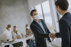 Two masked businessmen shaking hands photo