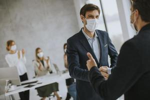 Two masked businessmen meeting photo