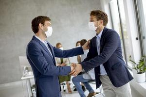 Two masked businessmen making agreement photo