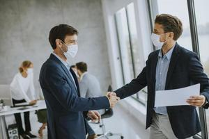 Two masked businessmen shaking hands in agreement photo
