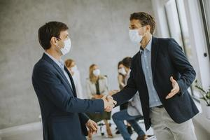 Two masked men shaking hands photo