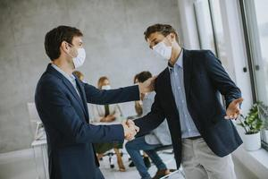 Two masked men making business agreement photo