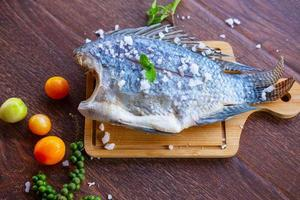 Delicious fresh fish on dark background. Fish with aromatic herbs, diet, or cooking concept. photo