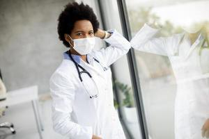 Doctor with mask leaning against window and looking at camera photo