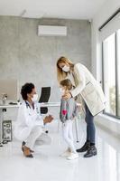 Pediatrician giving child a checkup photo