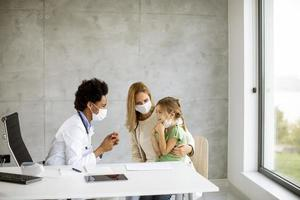 Pediatrician examining little girl with parent present photo