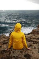 Young woman dressed in yellow raincoat sitting on the cliff looking at big waves photo