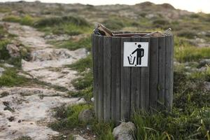 Wooden trash or litter bin in coastal areas near the sea photo