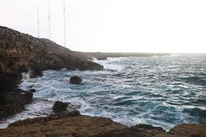 Waves hitting the rocky cliffs on a beach located in Cyprus photo