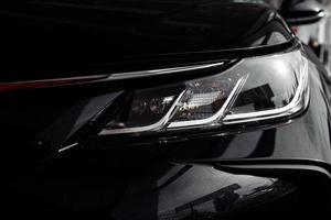 Faro del moderno y prestigioso coche negro de cerca foto