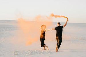 Guy and a girl in black clothes hug and run on the white sand with orange smoke photo