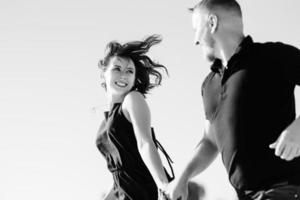 Young couple a guy and a girl with joyful emotions in black clothes walk through the white desert photo