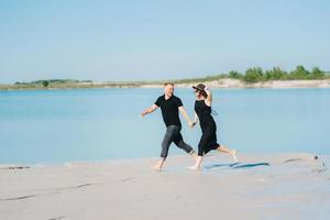 Young couple a guy with a girl in black clothes are walking on the white sand photo