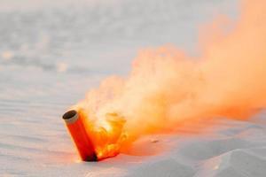 Bomba de humo con humo naranja atascado en la arena. foto