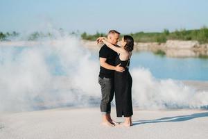chico y una chica vestida de negro se abrazan dentro de humo blanco foto