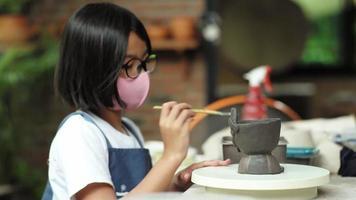 Chica asiática con máscara facial haciendo trabajos de arcilla en el aula video