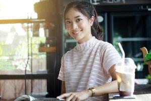 Mujer asiática leyendo un libro para relajarse en la cafetería. foto