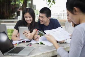 estudiantes asiáticos que usan tabletas y portátiles en el campus foto