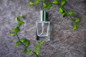 Vista superior de una botella de perfume rodeada de hojas verdes. foto
