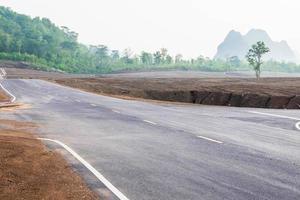 un camino largo y recto que conduce a una montaña foto