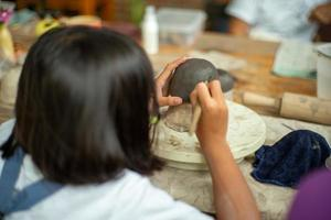 Closeup clay work on the plaster model with motion blurred hands of student learning in the workshop classroom photo