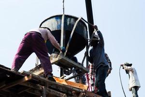 Grupo de trabajadores cargando el cemento mezclado desde el balde de acero en el sitio de construcción. foto