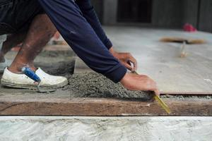 Worker using the wooden trowel during installing the floor tiles photo