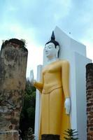 Statue of Buddha in the ancient temple with blue sky background. photo