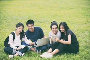 estudiantes asiáticos que estudian en la hierba foto