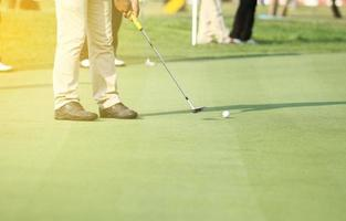 Golfer putting on the green photo
