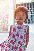 Portrait of Asian little girl looking at the camera with sunlight in the background photo