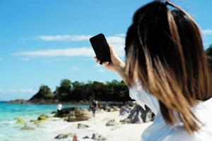 Back portrait of female tourist holding a mobile phone and taking a selfie picture with a blurred seascape and people in the background. Selective focus on blank screen of mobile held by the woman for a selfie. photo