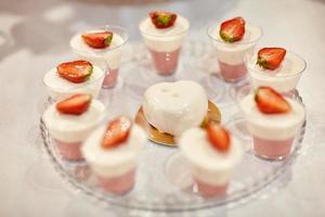 barra de chocolate de boda con postres rosados y blancos foto