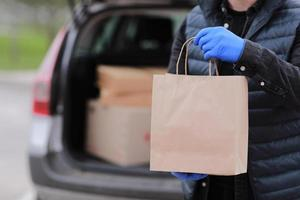 Cropped delivery man in gloves holds paper bag near the car photo