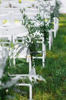 Decorated white chairs at a wedding ceremony photo