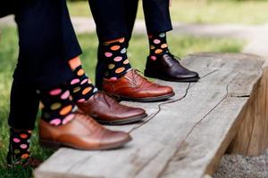 Feet of the groom and friends of the groom with funny colored socks photo