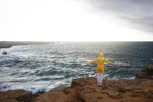 Mujer joven vestida con impermeable amarillo de pie con los brazos extendidos mientras disfruta del hermoso paisaje del mar foto