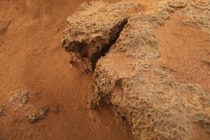 Orilla rocosa con arena roja del mar mediterráneo foto