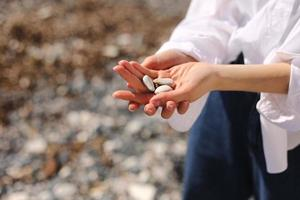 Woman's hands holds pebble stones photo