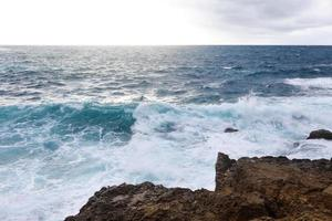 Waves hitting the rocky cliffs on the beach located in Cyprus photo