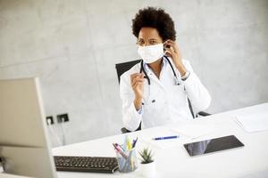 Doctor putting on mask at desk photo