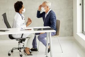 Mature man discussing head pain with doctor photo