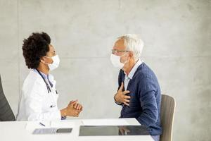 Mature man discussing chest pain with doctor photo