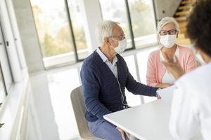 Mature couple at doctor's office wearing masks photo