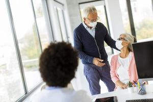Mature couple wearing masks and talking to doctor photo